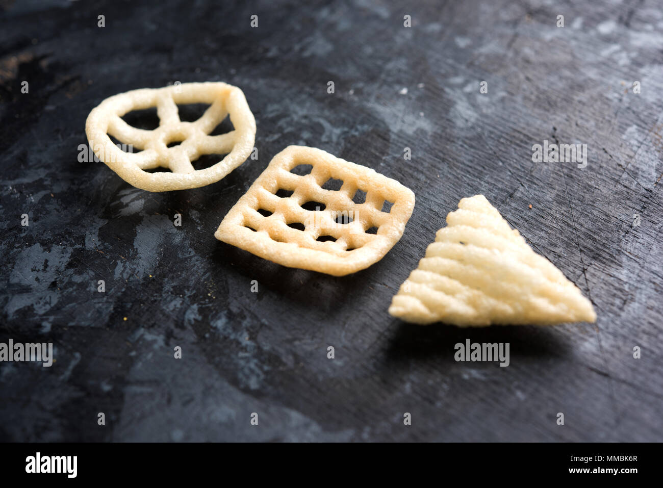 Indian crunchy fryums or papad snack in wheel, square and triangle shape. selective focus - Stock Image