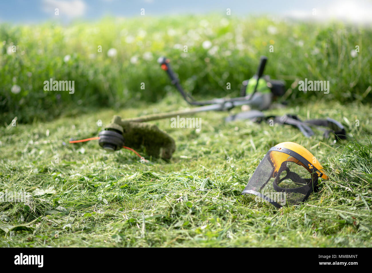 String trimmer and protective face mask on mown grass, growing grass and the blue sky on the background - Stock Image