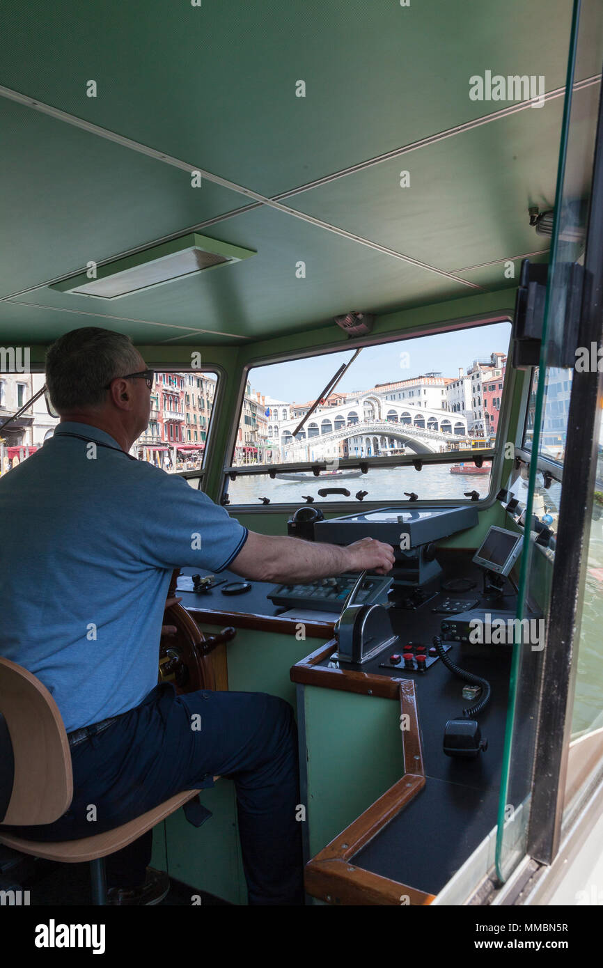 Vaporetto or waterbus captain piloting his boat approaching the Rialto Bridge, Grand Canal, Venice, Italy in a first person POV through the windscreen - Stock Image