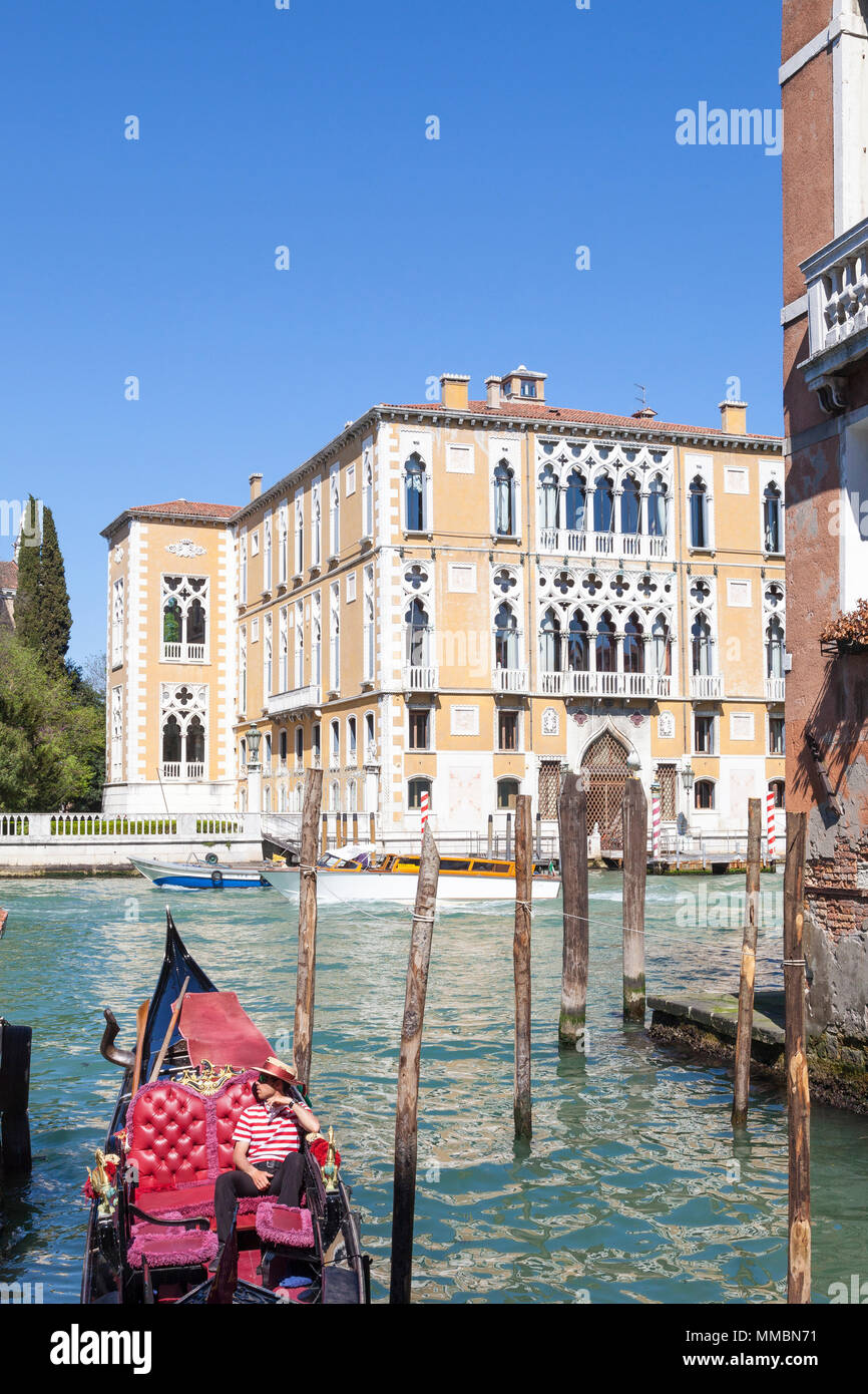 Gondolier relaxing in his gondola on the Grand Canal with Palazzo Cavalli-Franchetti behind him,  Venice, Veneto, Italy as he waits for tourists - Stock Image