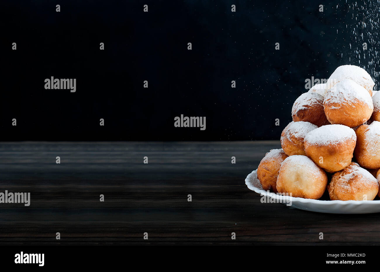sweet donuts laid out pyramid sprinkled with powdered sugar on the plate ,on dark background , copy space - Stock Image