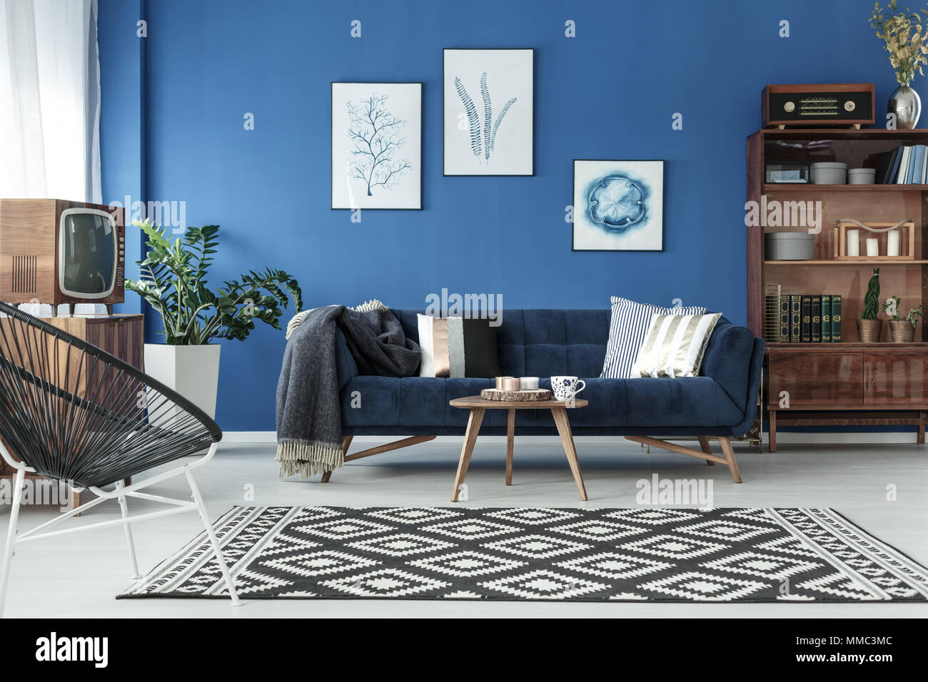 Blue up-to-date decor of lounge with blue sofa and patterned carpet - Stock Image