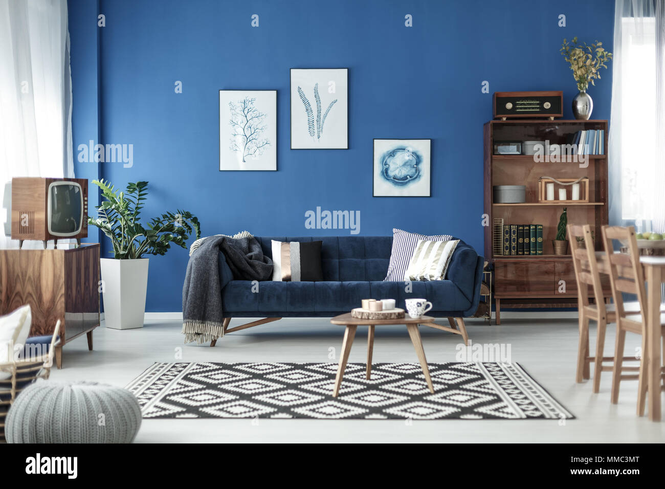 Retro style cozy living room with blue walls and white floor ...