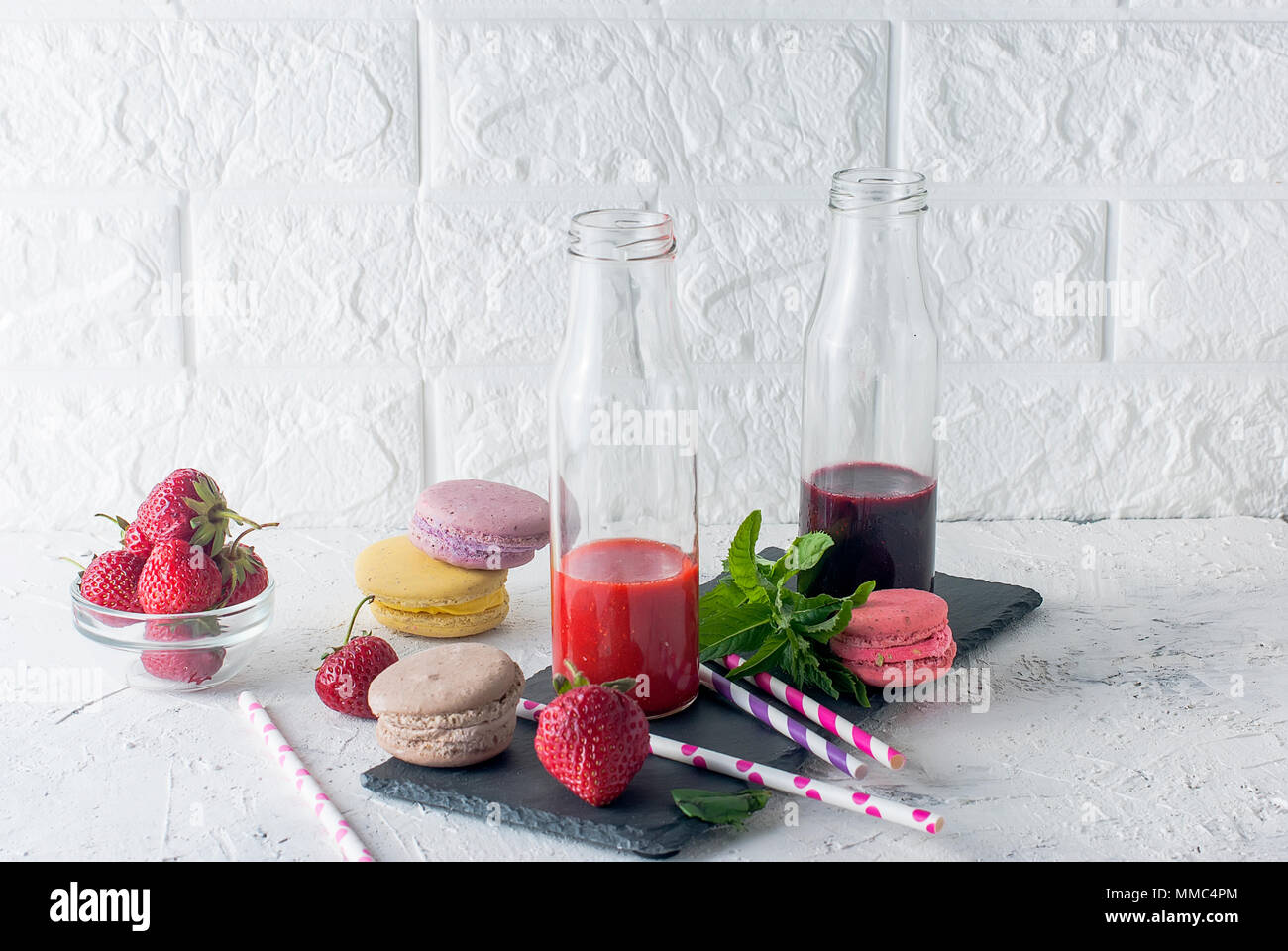 Refreshing strawberry and blueberry smoothies in a glass bottle close-up and  bowl of fresh strawberrieson the table. - Stock Image