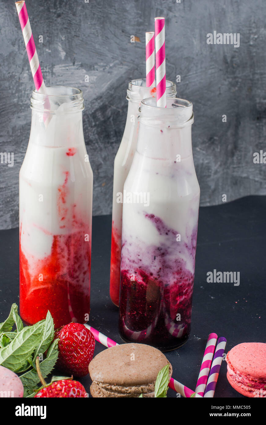 Refreshing strawberry and blueberry smoothies in a glass bottle close-up and  bowl of fresh strawberries on the table. - Stock Image