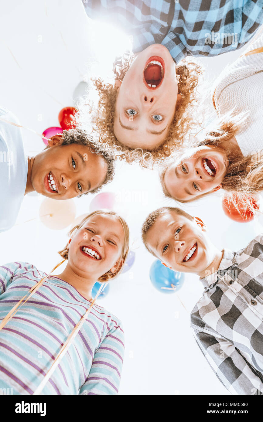 Group of children standing in circle and laughing - Stock Image