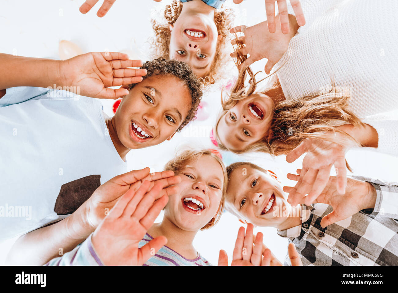 Group of happy children waving at the camera - Stock Image