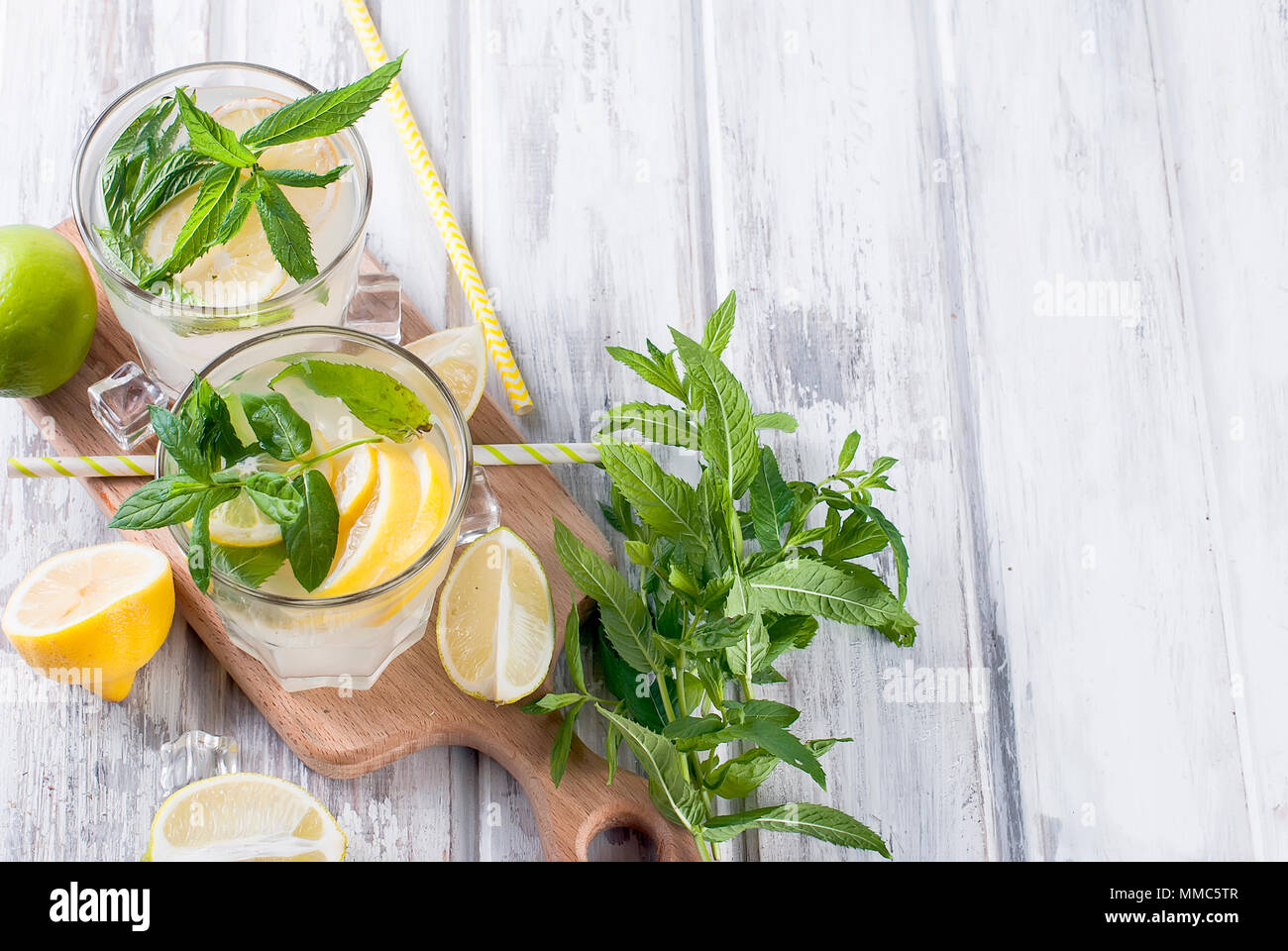 Fresh homemade lemonade in glass with ice and mint, ingredients for cocktail, lemon and lime slices, mint leaves on white wooden table, copy space - Stock Image