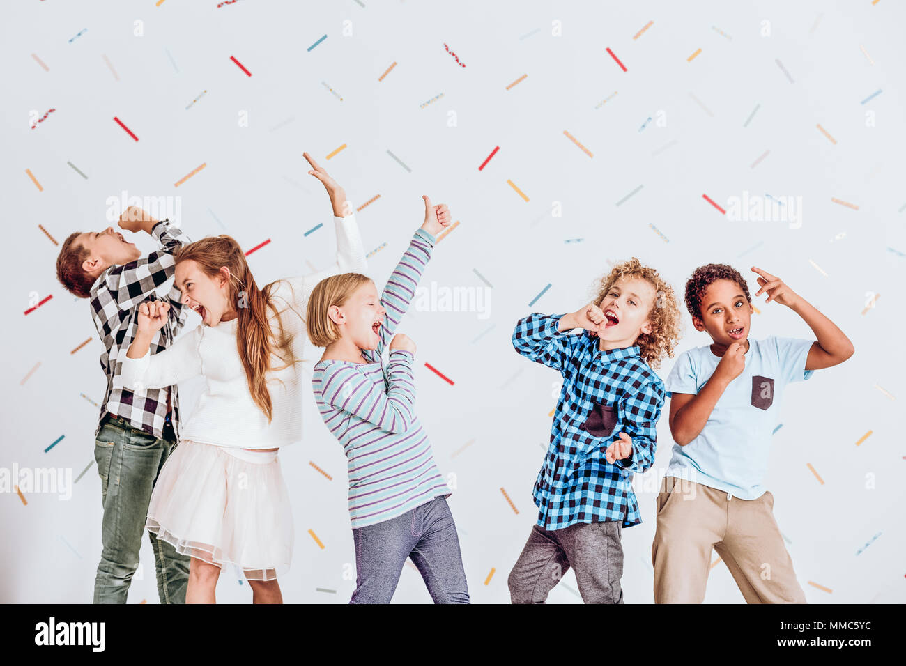 Group of happy boys and girls pretending to sing at a party - Stock Image