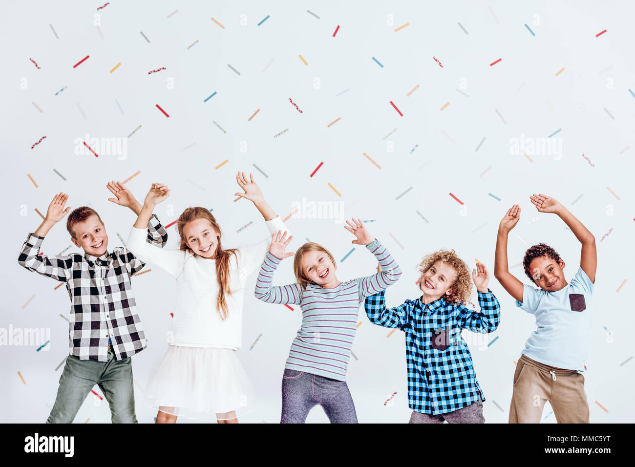 Group of kids standing with their hands up and having fun - Stock Image