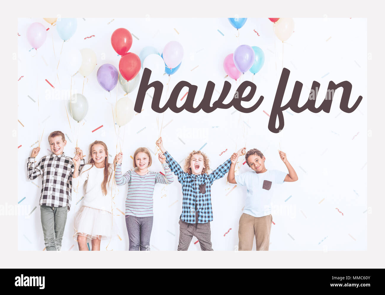 Writing 'have fun' and happy kids standing with balloons in a room - Stock Image