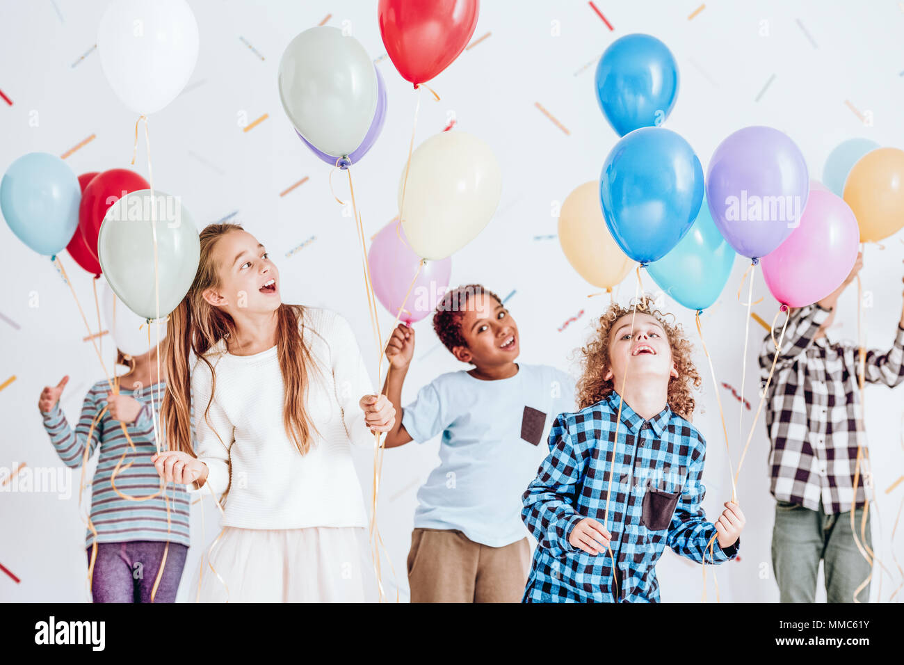 Group of kids having a party and dancing with balloons in their hands - Stock Image
