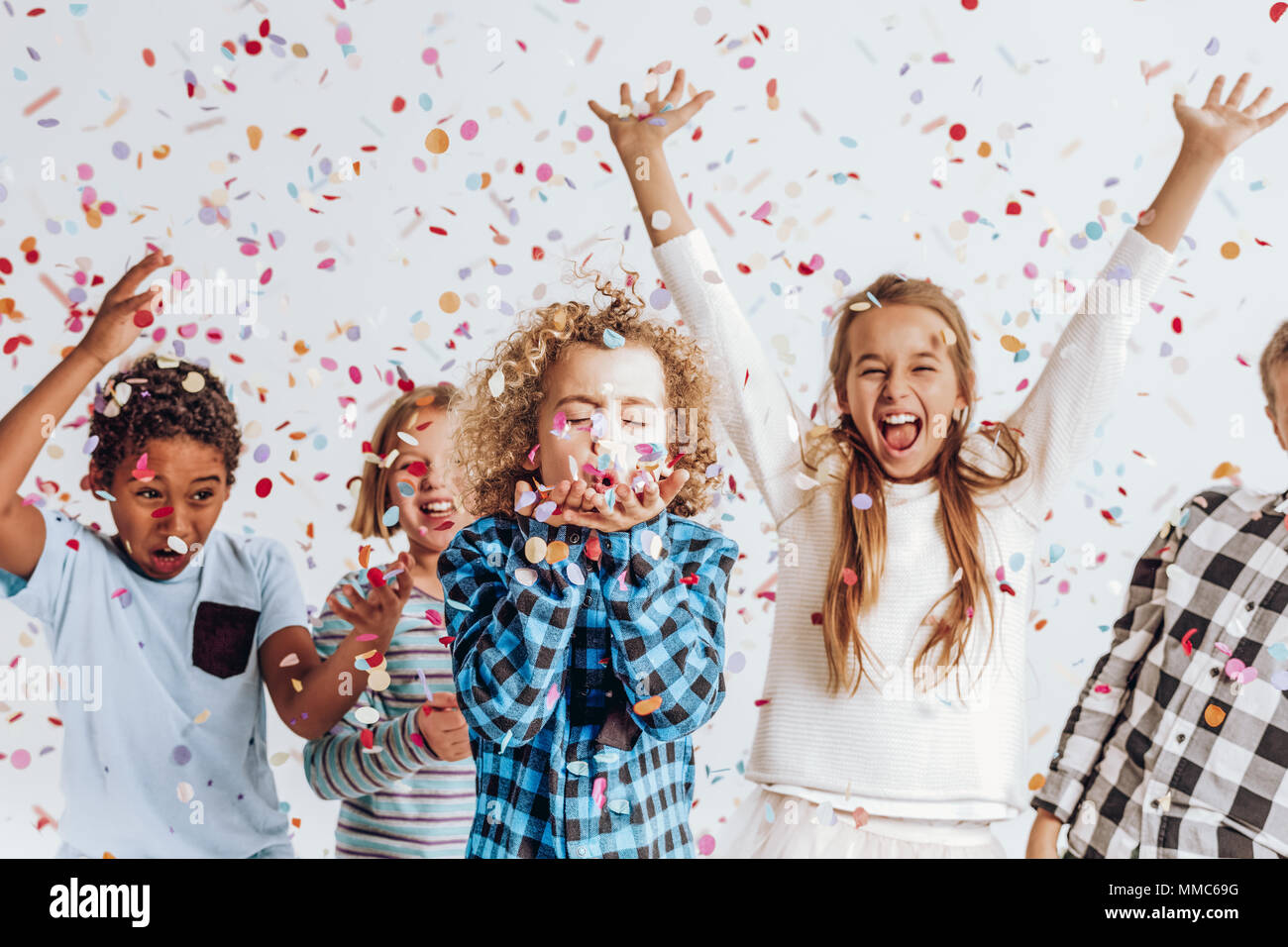 Happy kids having fun in a room full of confetti - Stock Image