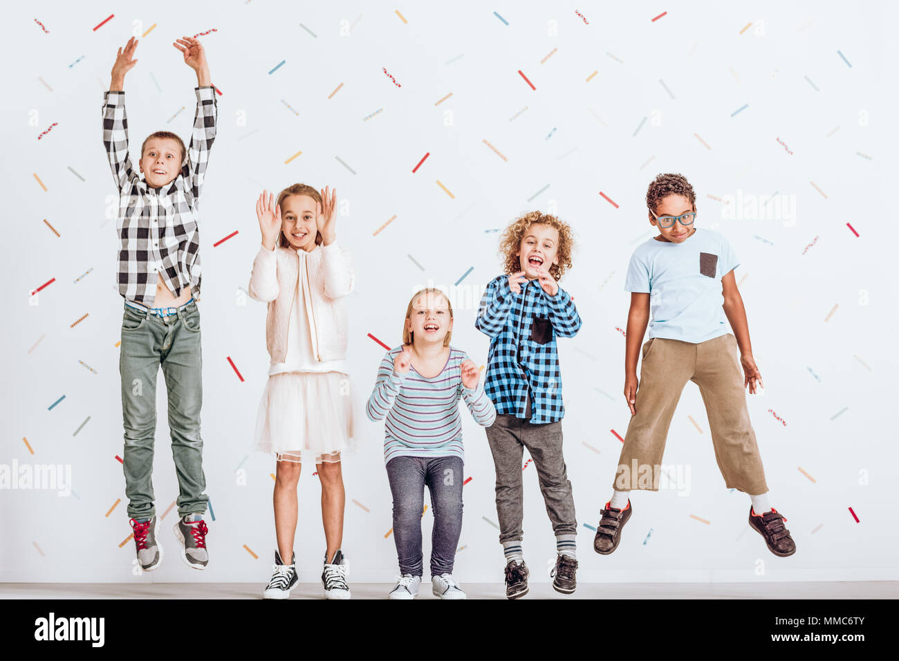 Happy girls and boys jumping in a room - Stock Image