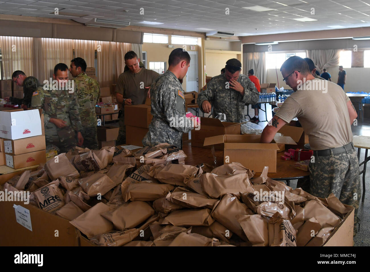Soldiers with the Company C., 6th Battalion, 101st General Support Aviation Battalion, 101st Combat Aviation Brigade, 101st Airborne Division (Air Assault) repackage food and water at a community center October 4, 2017 in Ceiba, Puerto Rico. The Soldiers are assisting FEMA with relief efforts after the devastating effects of Hurricane Maria. (U.S. Army photo by Sgt. Marcus Floyd, 101st Combat Aviation Brigade) - Stock Image