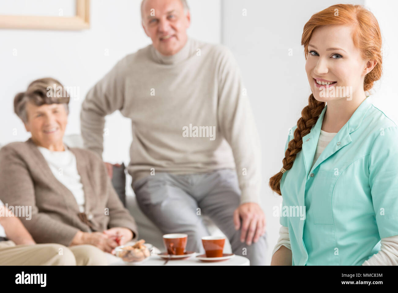 Smiled elder charges with their red-haired nurse - Stock Image
