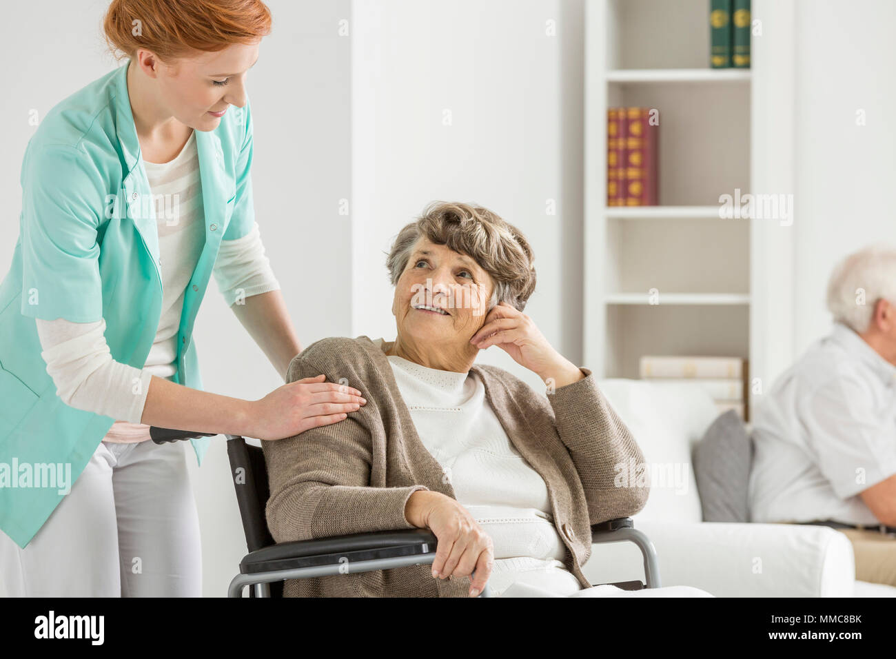 Woman on wheelchair looking at her young nurse - Stock Image