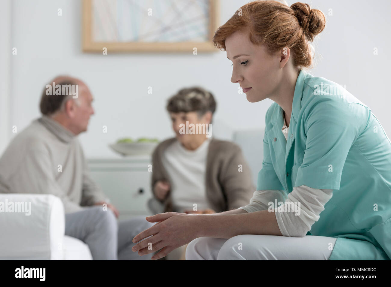Put out young nurse at retirement home - Stock Image