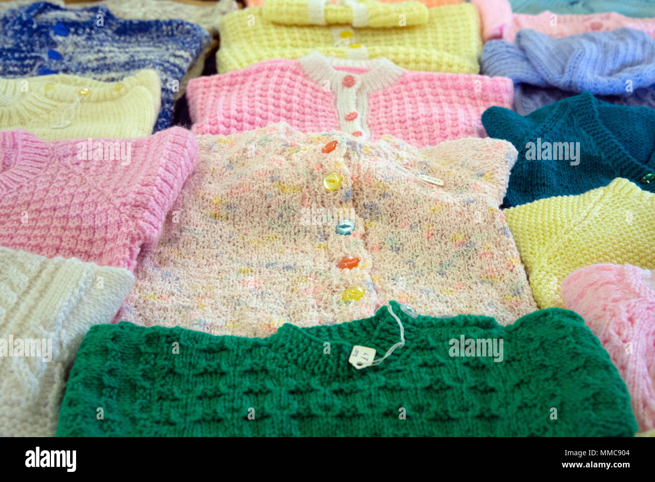 pristine new hand-knitted hand-made woollen cardigans and jumpers on sale in an english church hall fundraising for good causes for the parish council - Stock Image