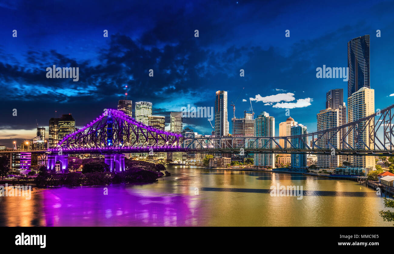 Vibrant night time and day time panorama of Brisbane city with purple lights on Story Bridge, Australia Stock Photo