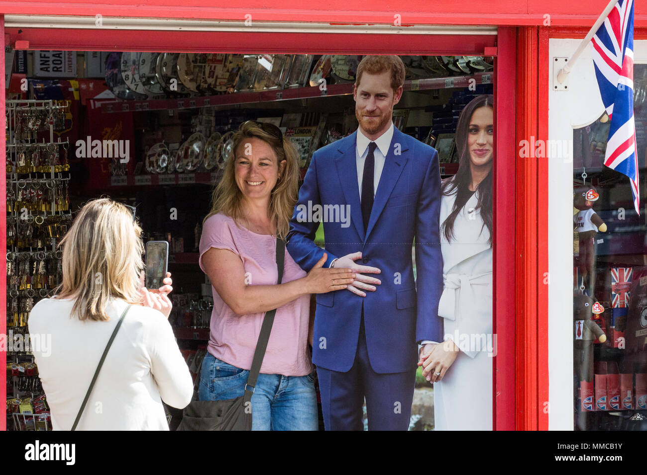 Windsor, UK. 10th May, 2018. Tourists take pictures with cardboard cutouts of Prince Harry and Meghan Markle in advance of the royal wedding at Windsor Castle on 19th May. Credit: Mark Kerrison/Alamy Live News - Stock Image