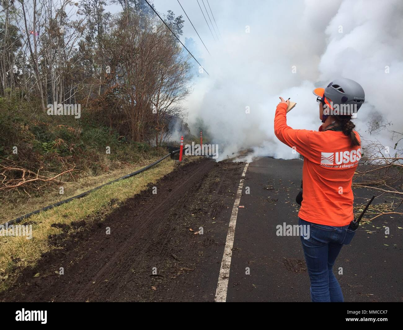 Leilani Estates, Hawaii. May 9, 2018. A U.S. Geologic Survey scientist records a new fissure venting steam along Pohoiki Road caused by the Kilauea volcano eruption May 9, 2018 in Leilani Estates, Hawaii. The recent eruption continues destroying homes, forcing evacuations and spewing lava and poison gas on the Big Island of Hawaii. Credit: Planetpix/Alamy Live News - Stock Image