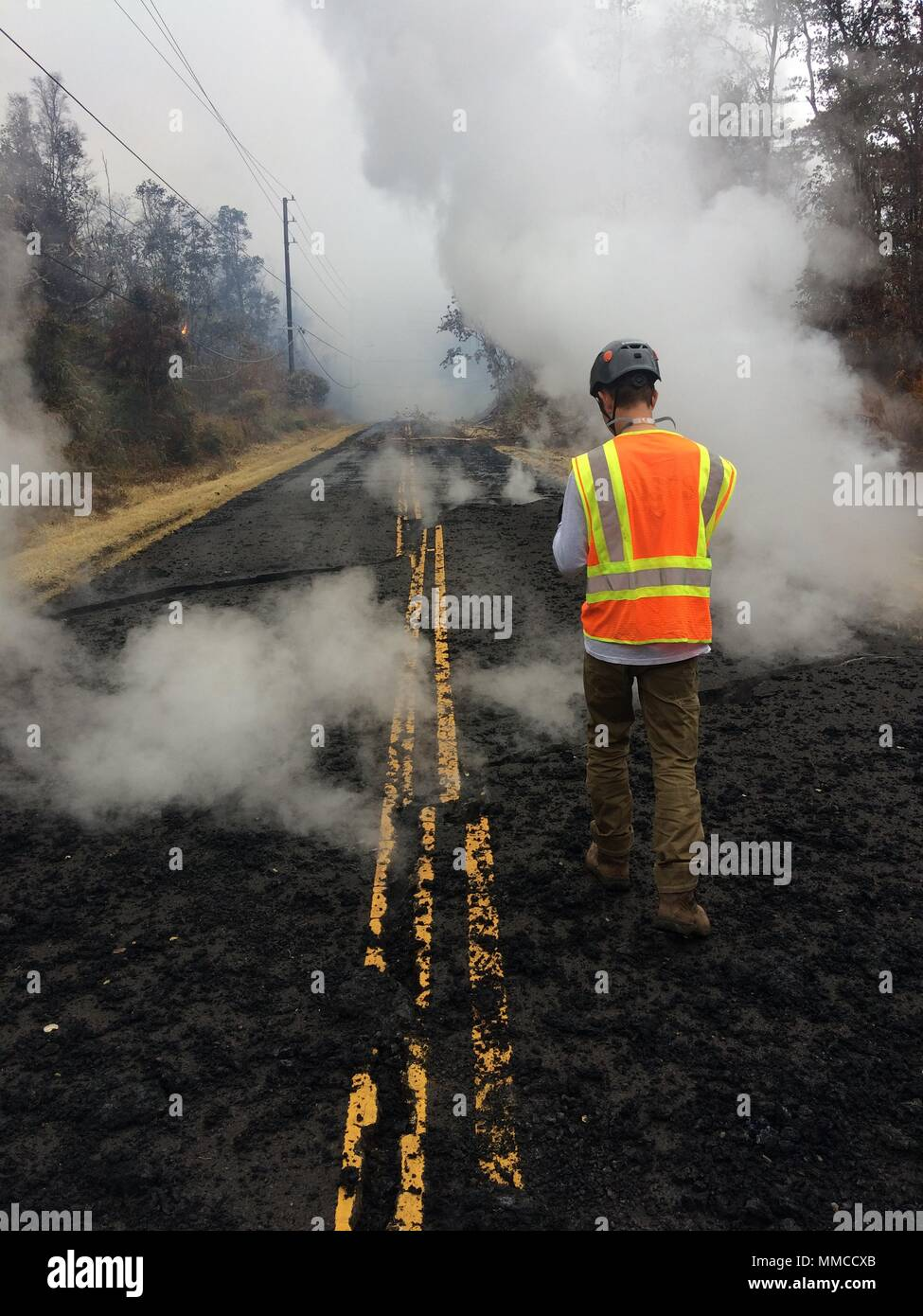 Leilani Estates, Hawaii. May 9, 2018. A U.S. Geologic Survey scientist records ground cracks venting steam along Leilani Street caused by the Kilauea volcano eruption May 9, 2018 in Leilani Estates, Hawaii. The recent eruption continues destroying homes, forcing evacuations and spewing lava and poison gas on the Big Island of Hawaii. Credit: Planetpix/Alamy Live News - Stock Image