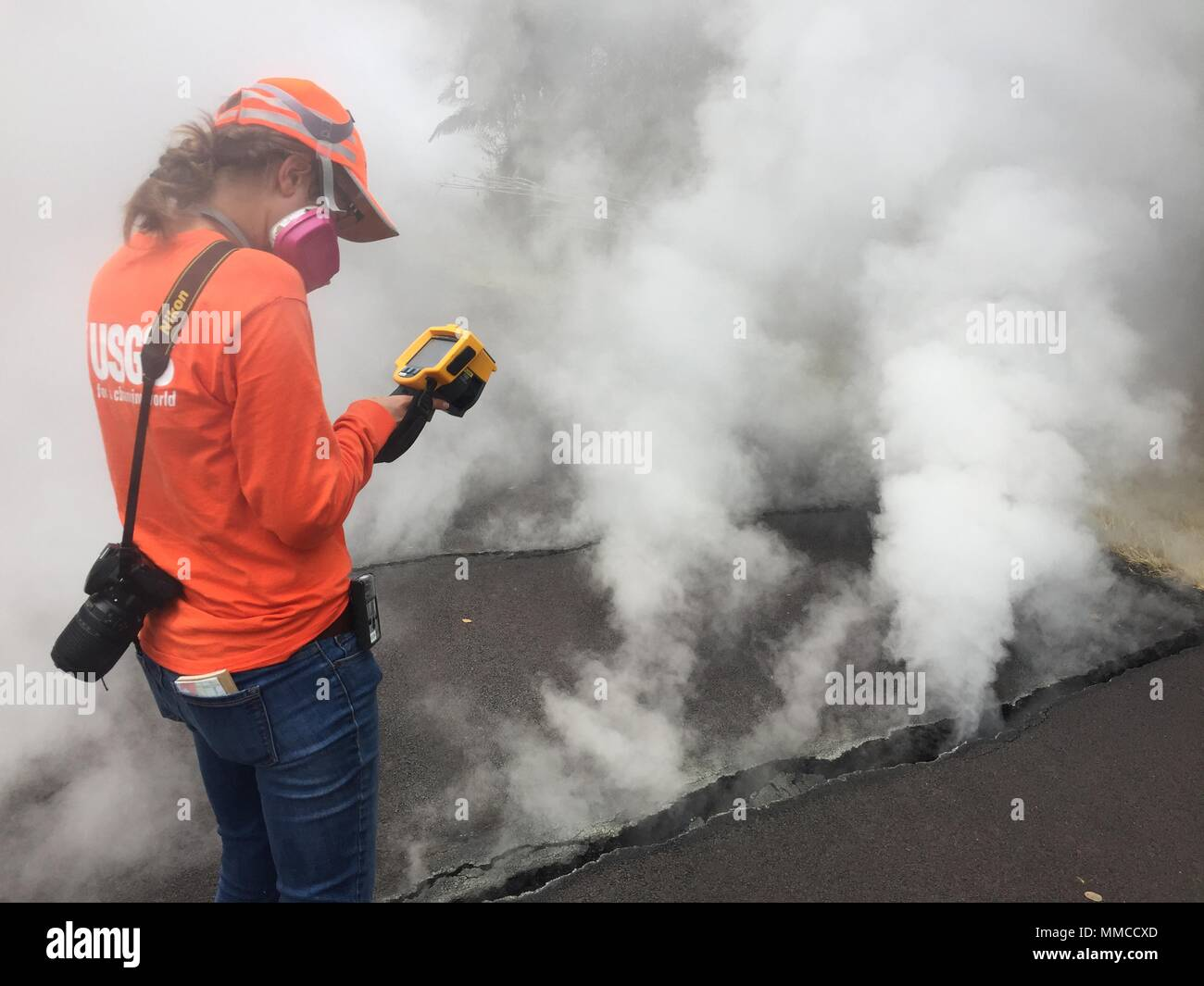 Leilani Estates, Hawaii. May 9, 2018. A U.S. Geologic Survey scientist records temperatures from ground cracks venting steam along Nohea Street caused by the Kilauea volcano eruption May 9, 2018 in Leilani Estates, Hawaii. The recent eruption continues destroying homes, forcing evacuations and spewing lava and poison gas on the Big Island of Hawaii. Credit: Planetpix/Alamy Live News - Stock Image
