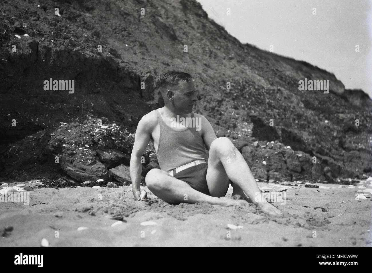1930s, adult man in swimwear of the day lying on a sandy beaech, England, UK. - Stock Image