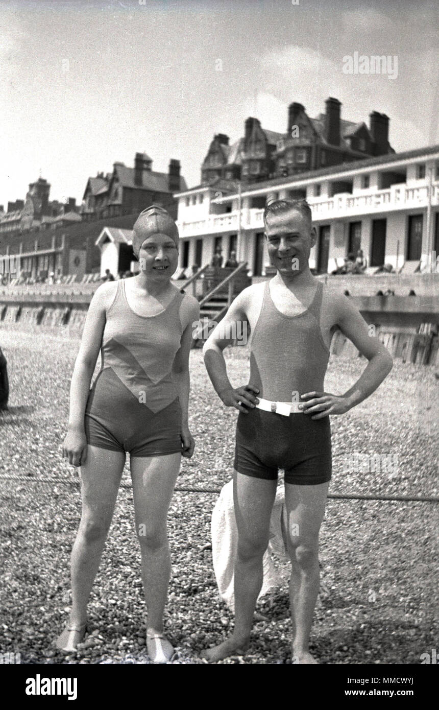 1930s, man and woman in swimwear of the day standing together on a pebbly beach at the seafront, england, uk. - Stock Image