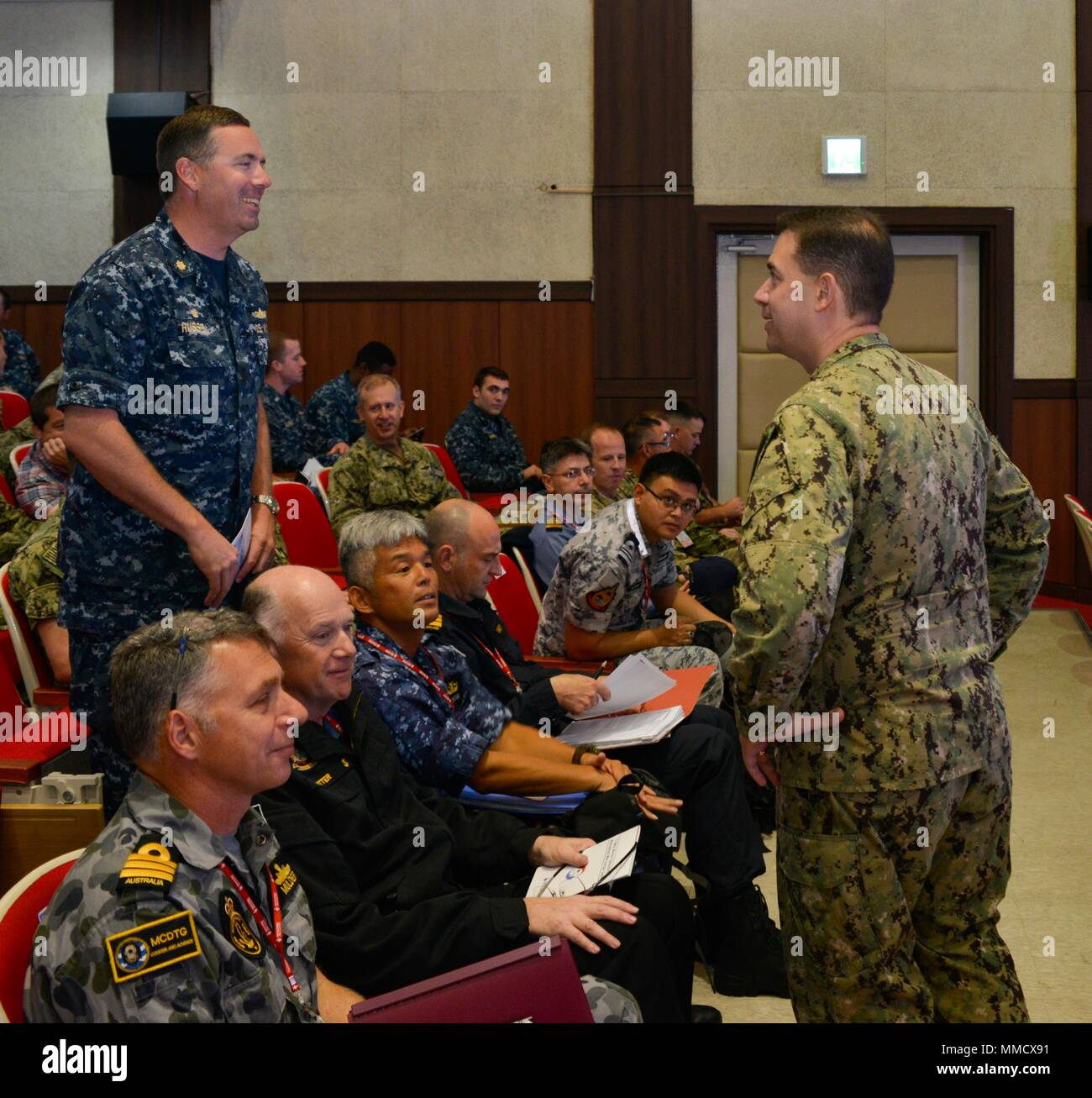 171012-N-TB148-007 BUSAN, Republic of Korea (Oct. 12, 2017) Rear Adm. Brad Cooper, commander, U.S. Naval Forces Korea (CNFK), speaks with LCDR William A. Russell, commanding officer aboard the Avenger-class mine countermeasures ship USS Chief (MCM 14), at the fourth annual Mine Countermeasures (MCM) Symposium. The symposium's purpose is to enhance interoperability, coordination and training in mine countermeasures capabilities between U.S., ROK, and UNC SS forces. (U.S. Navy photo by Mass Communication Specialist Seaman William Carlisle) Stock Photo
