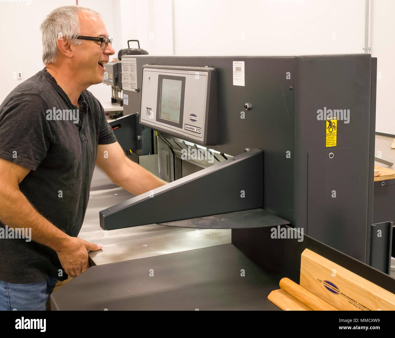 Dennis Fickel, Department of Energy Material Office, Naval Supply Systems Command, Weapon Systems Support, uses a bulk paper cutter in the newly opened print center, Oct. 11, in Mechanicsburg, Pa. - Stock Image