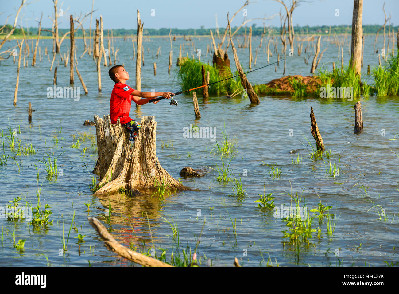 Chachoengsao, Thailand - December 8, 2011, Fisherboy fishing by using fishing pole to fish in rural swamp in Chachoengsao, Thailand - Stock Image