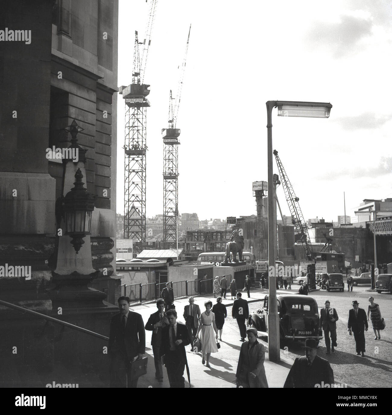 1960s, rail commuters walking towards waterloo railway station, on the south bank, London, England, UK. A crane can be seen on the foreground, as massive construction or building works were taking pace at this time on the South Bank of the River Thames, including the building of the Shell Centre, an enormous office tower block. - Stock Image