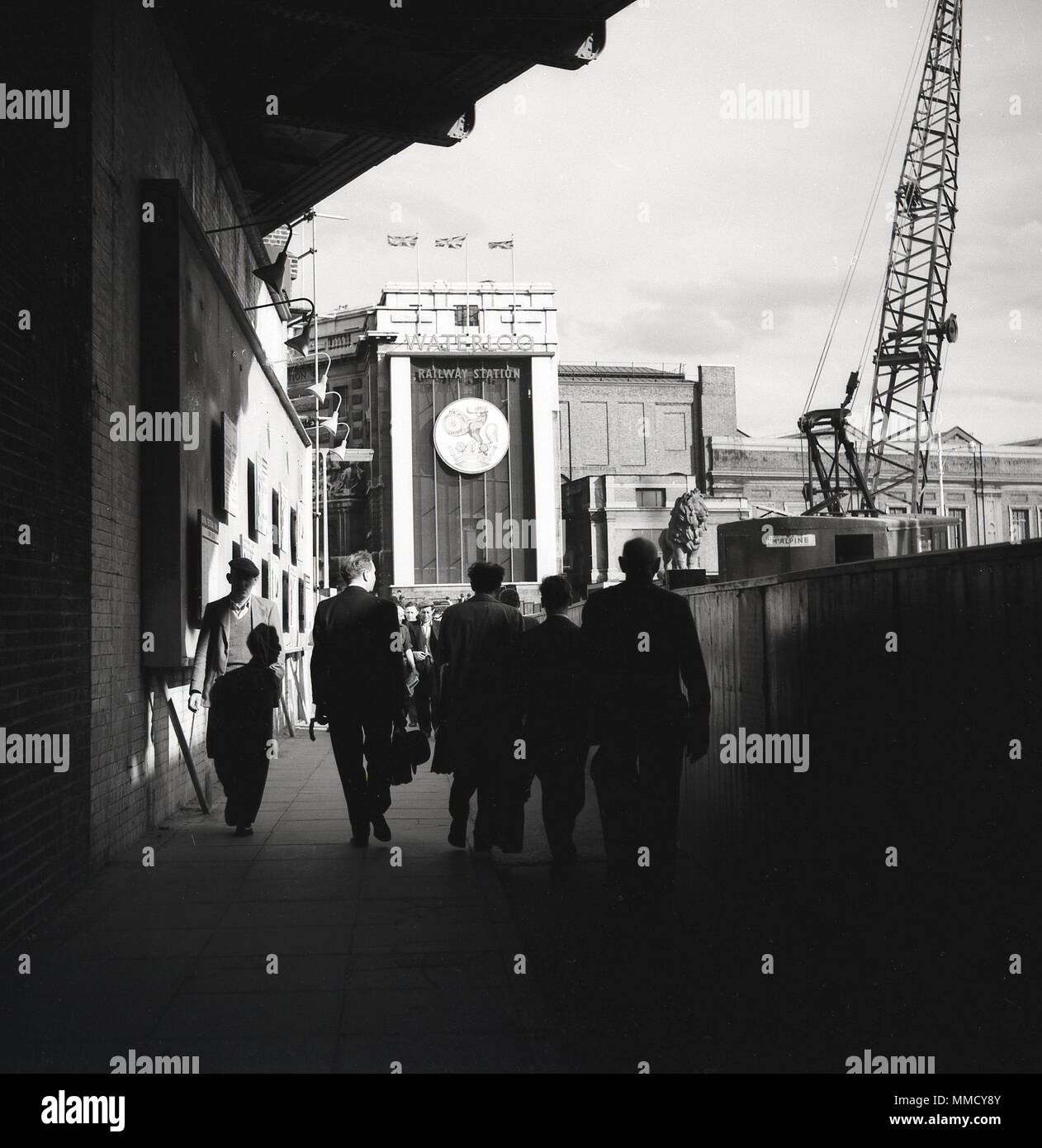 1960s, commuters walking on a concourse towards waterloo railway station, on the south bank, London, England, UK. A crane can be seen on the foreground, as massive construction or building works were taking pace at this time on the South Bank of the River Thames, including the building of the Shell Centre, an enormous office tower block. - Stock Image