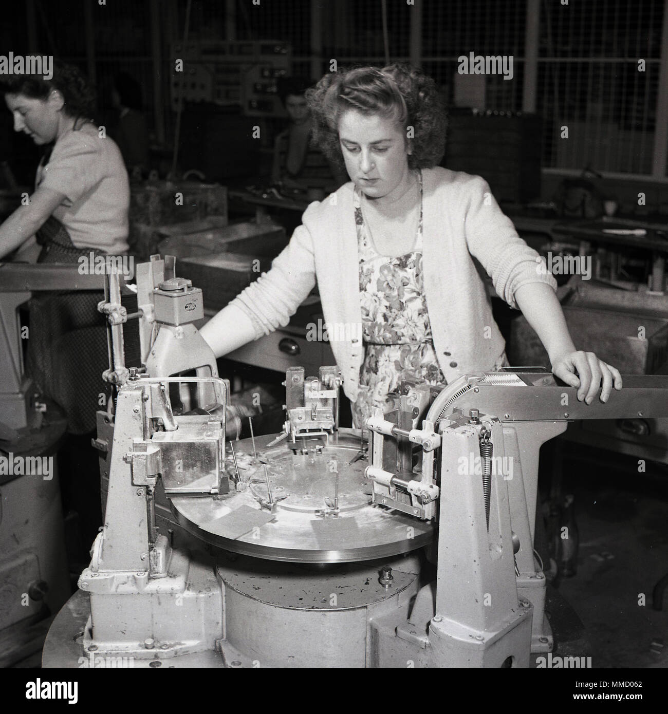 1950s, woman in ordinary day clothes working on a factory floor with a large engineering machine tool, England, UK. With the shortage of male workers following WW2, many woman continued in traditional male orientated jobs they had taken on temporarily during the war effort. - Stock Image