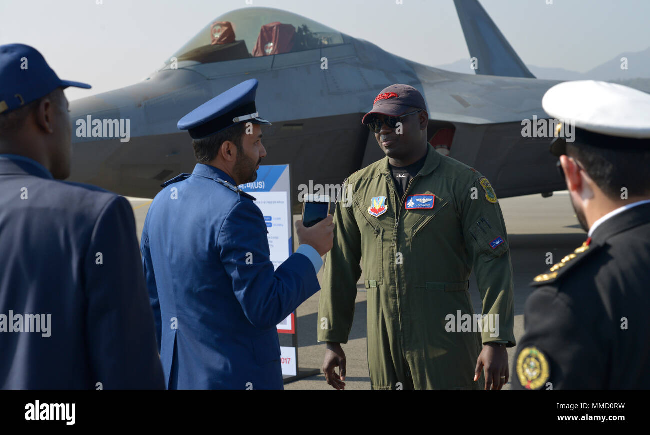 U.S. Air Force Maj. Paul Lopez, Air Combat Command F-22 Raptor Demonstration Team future pilot, talks to international military members about the capabilities of fifth-generation fighter aircraft during the Seoul International Aerospace and Defense Exhibition (ADEX) 2017 at the Seoul Airport, Republic of Korea, Oct. 17, 2017. The Seoul ADEX is the largest, most comprehensive event of its kind in Northeast Asia, attracting aviation and aerospace professionals, key defense personnel, aviation enthusiasts and the general public alike. (U.S. Air Force photo by Staff Sgt. Alex Fox Echols III) - Stock Image
