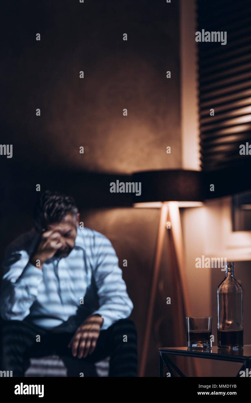 Silhouette of a stressed middle-aged man with problems sitting alone with his head down next to a bottle and a glass of alcohol in a dark room with wi - Stock Image
