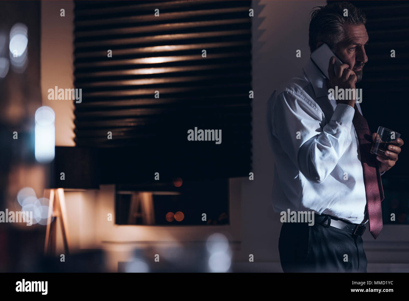 Tired and sad middle-aged businessman talking on the phone and holding a glass with alcohol while standing in a room with dimmed light and window blin - Stock Image
