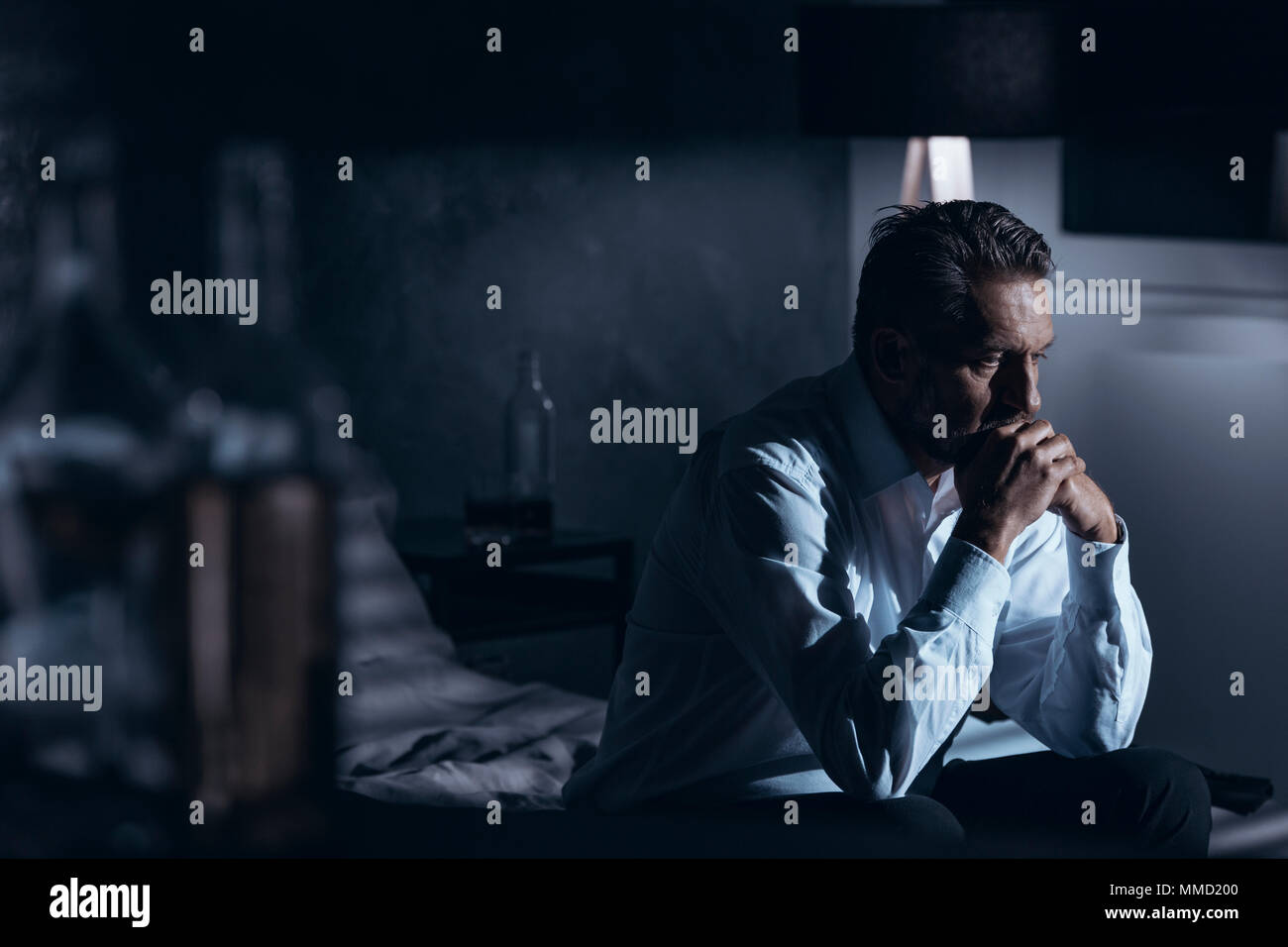 Portrait of a lonely mature man with depression sitting on a bed in a gray room with bottles of alcohol standing around - Stock Image