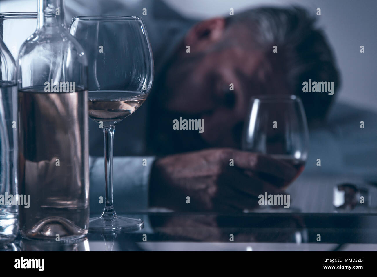 Close-up of a drunken desperate middle-aged man leaning on the table behind bottles and glasses with alcohol - Stock Image