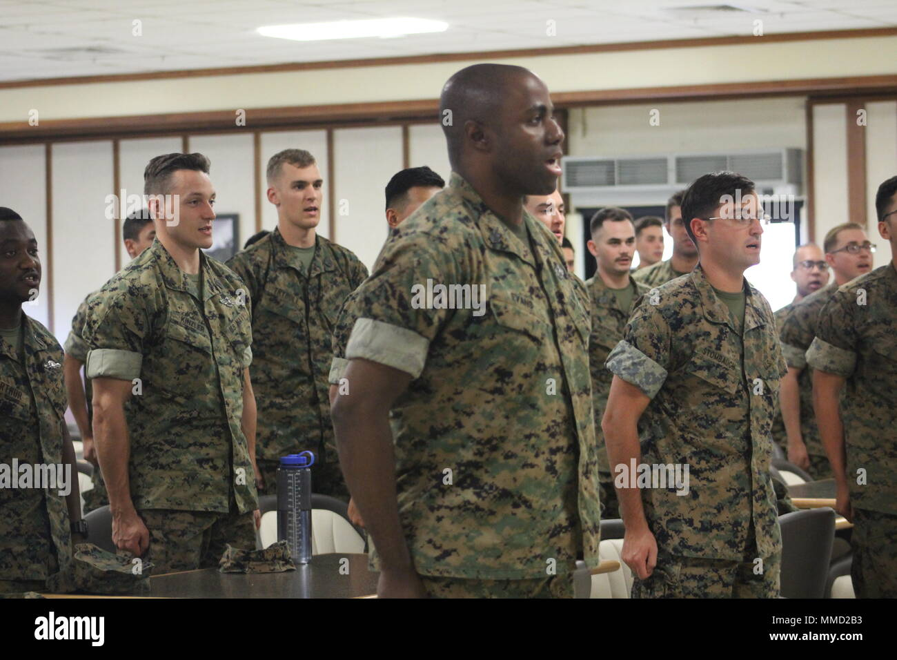 us navy sailors stand at attention for the sailors creed during a cake cutting ceremony at