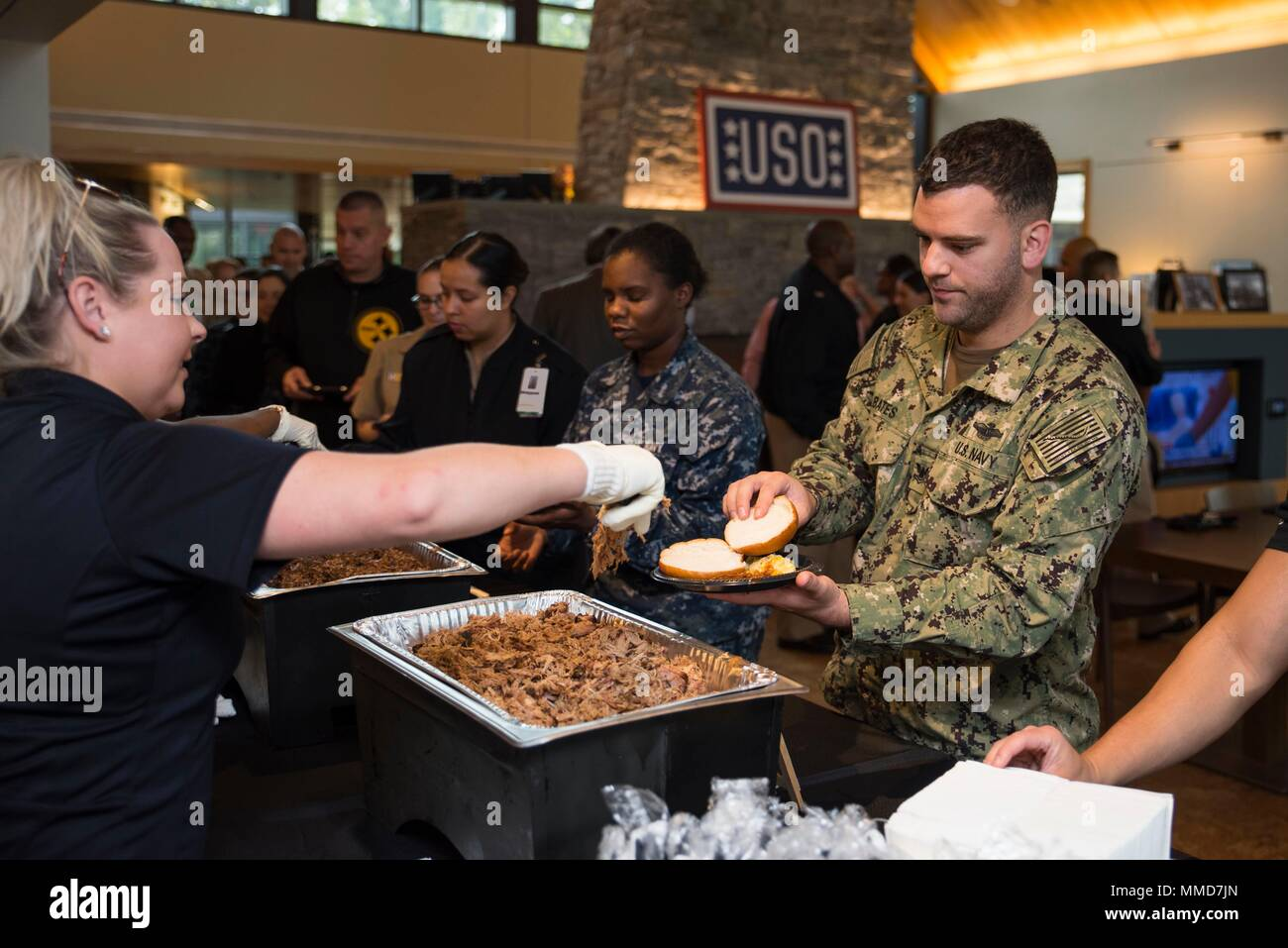 Service members are served food by staff from Mission Barbecue at the USO Family and Warrior Center at Bethesa Oct. 13.The Navy's birthday honors the brave men and women who conduct a wide range of combat, training, humanitarian, rescue and other missions worldwide, protecting the nation's interests, promoting its security, and helping to shape its history and culture. (U.S. Navy photo by Mass Communication Specialist 2nd Class William Phillips/Released) Stock Photo