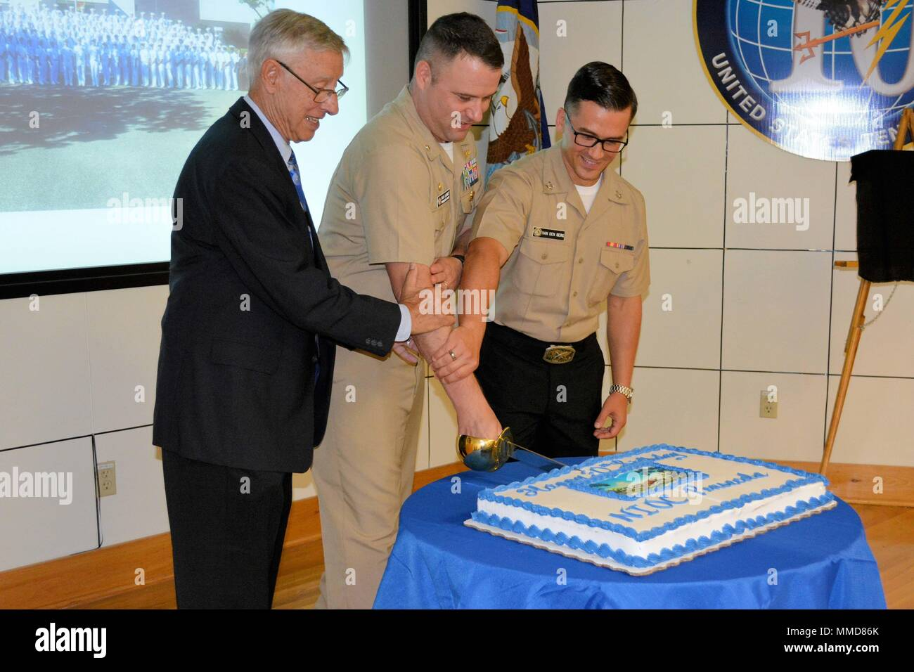 171006-N-AG811-024  PENSACOLA, Fla. (Oct. 6, 2017) – Retired Capt. Tom M. Pigoski, former officer in charge of Navy Security Group Detachment (NSGD) Pensacola (left), Cmdr. Paul D. Lashmet, commanding officer of Navy Information Operations Command (NIOC) Pensacola (center), and Cryptologic Technician (Networks) 3rd Class Jesse Van Den Berg cuts the cake for NIOC Pensacola's 30th birthday ceremony. NIOC Pensacola is a subordinate command of U.S. Fleet Cyber Command and comprises Task Group 103 of the U.S. 10th Fleet. (U.S. Navy photo by Cryptologic Technician (Networks) 1st Class Mark Jansson/R - Stock Image