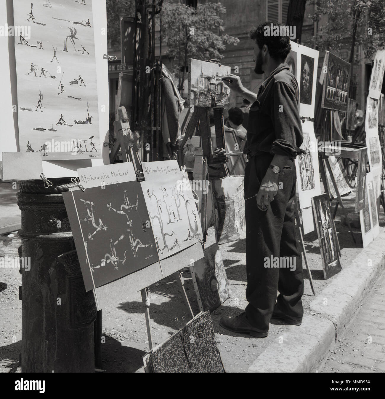 1950s, historical picture of a male street artist painting on a canvas at the Place du Tertre at Monmartre, Paris, France, an area famous for its artists and artistic history, - Stock Image
