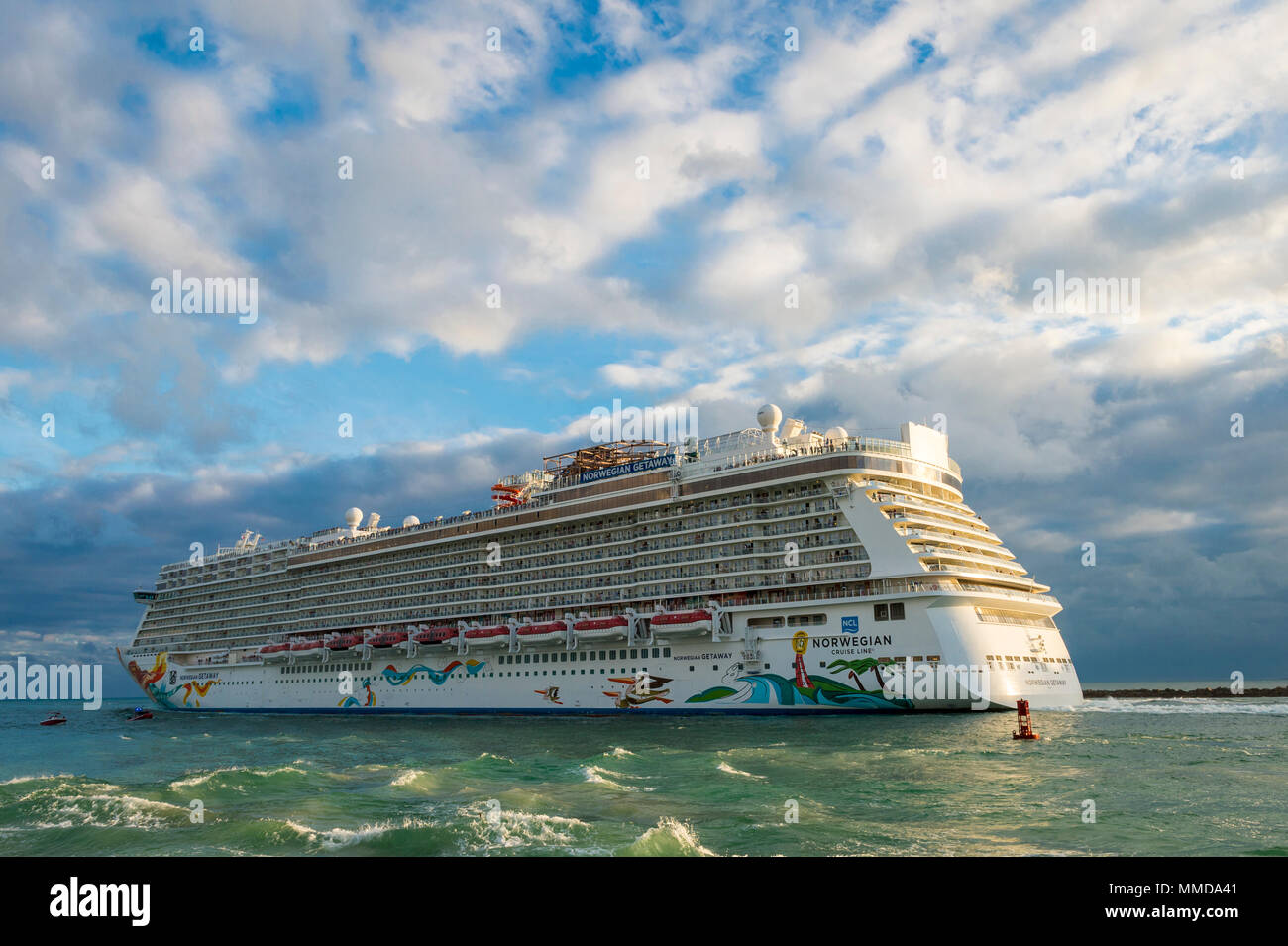 MIAMI, USA - CIRCA DECEMBER, 2017: Norwegian Getaway cruise ship passes South Beach as it leaves port at sunset. - Stock Image