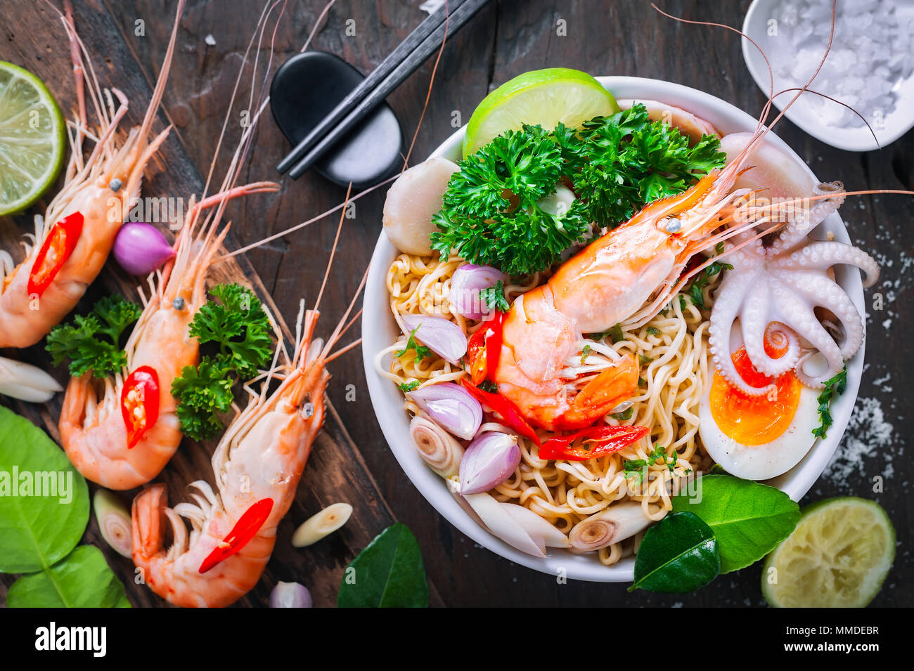 Hot seafood noodle in white bowl on wooden table - Stock Image
