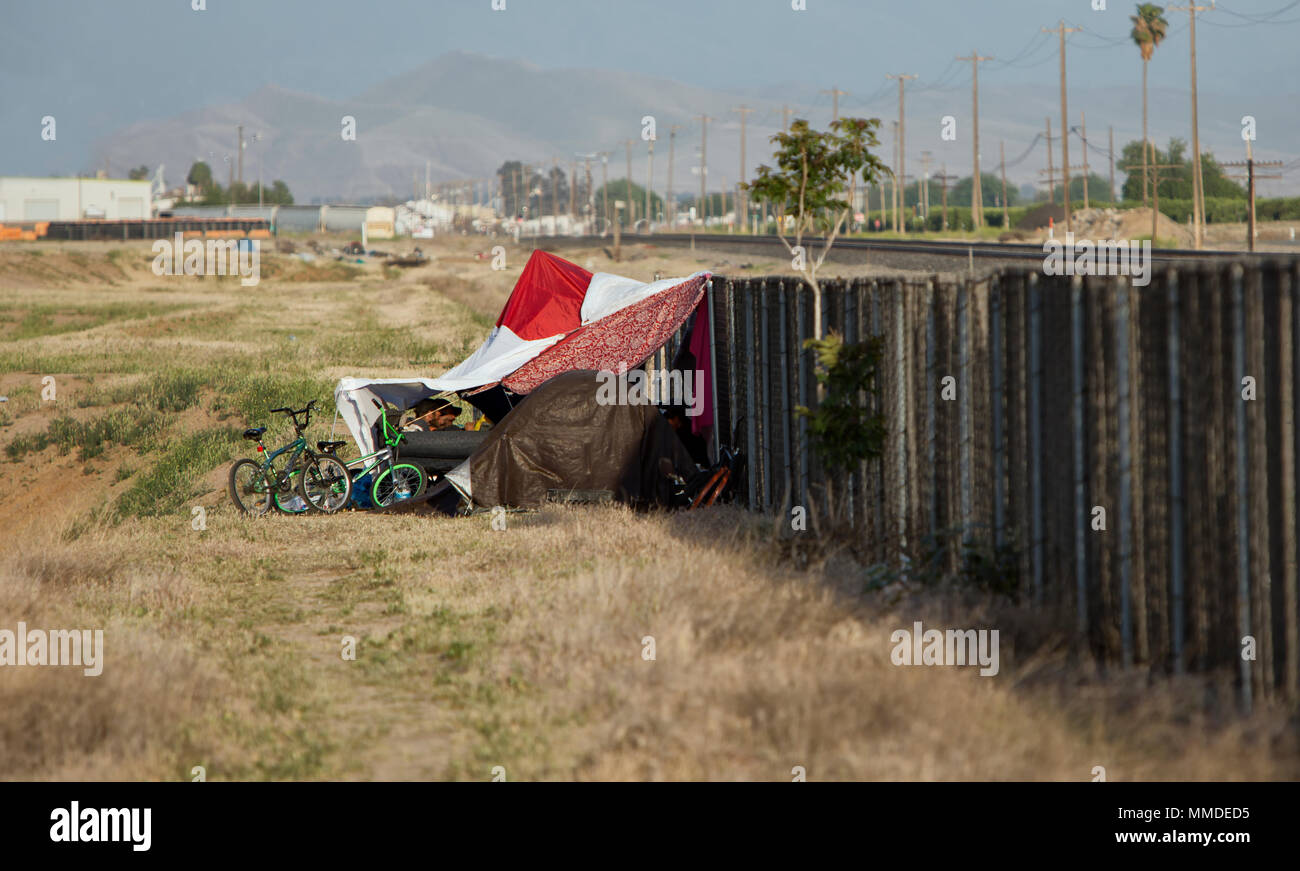 Homeless Camp against cyclone fence & railroad tracks. - Stock Image