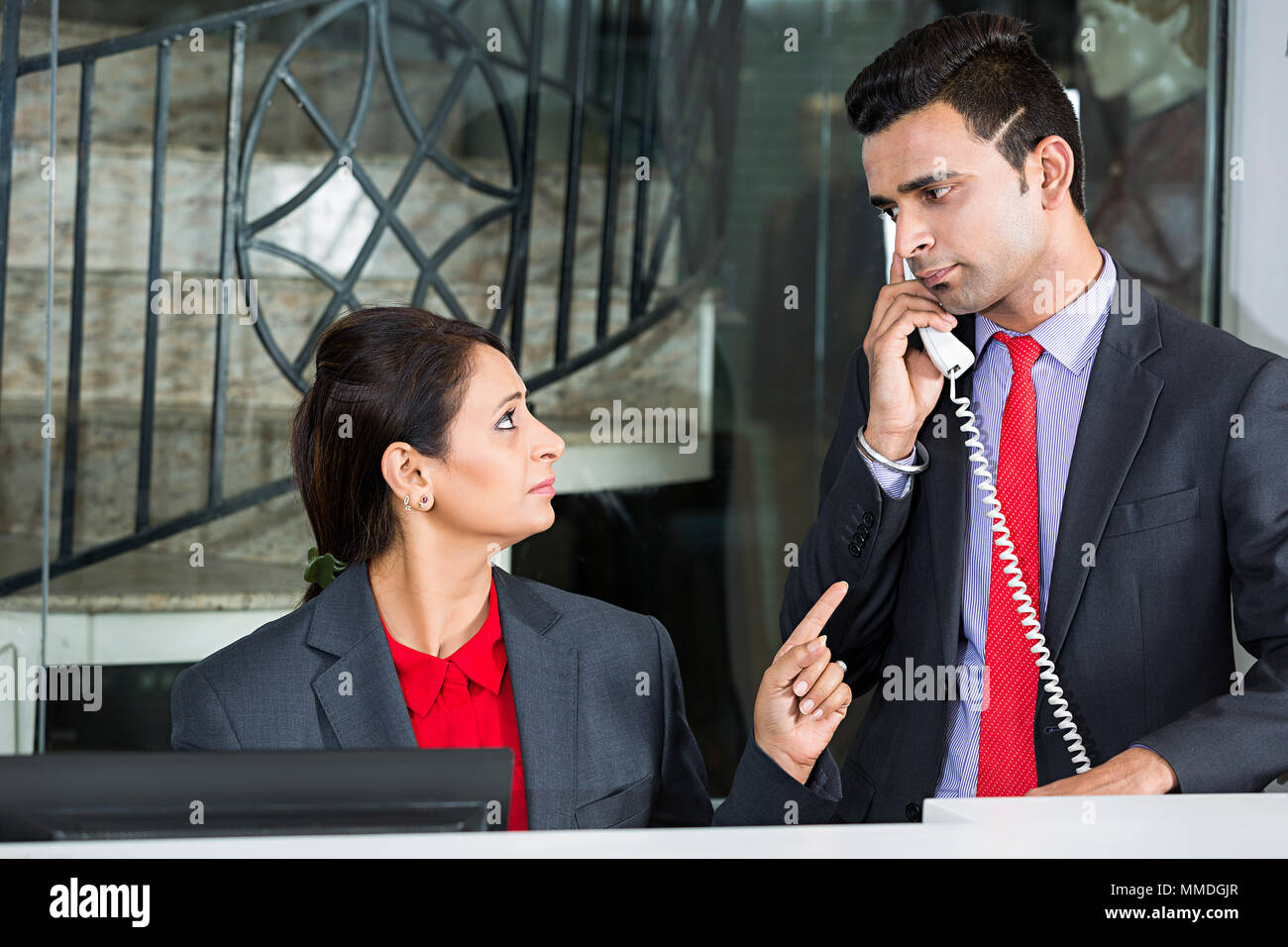 Two Receptionist Colleagues Employee Counter Talking Telephone Enquiry Hotel Reception - Stock Image