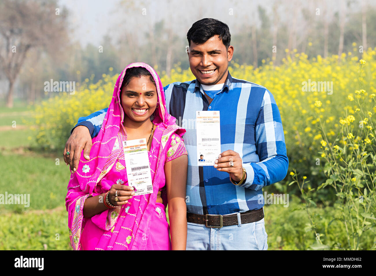 Happy villager couple together showing aadhaar card farm rural village